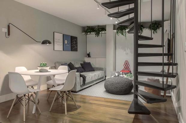 SALA DE JANTAR | Integrada, a sala de jantar se une à sala de estar e à cozinha. A mesa de jantar branca é da Tok&Stok, e as cadeiras são da By Art Design. A luminária é da Nova Home. (Foto: Mariana Orsi / Divulgação)