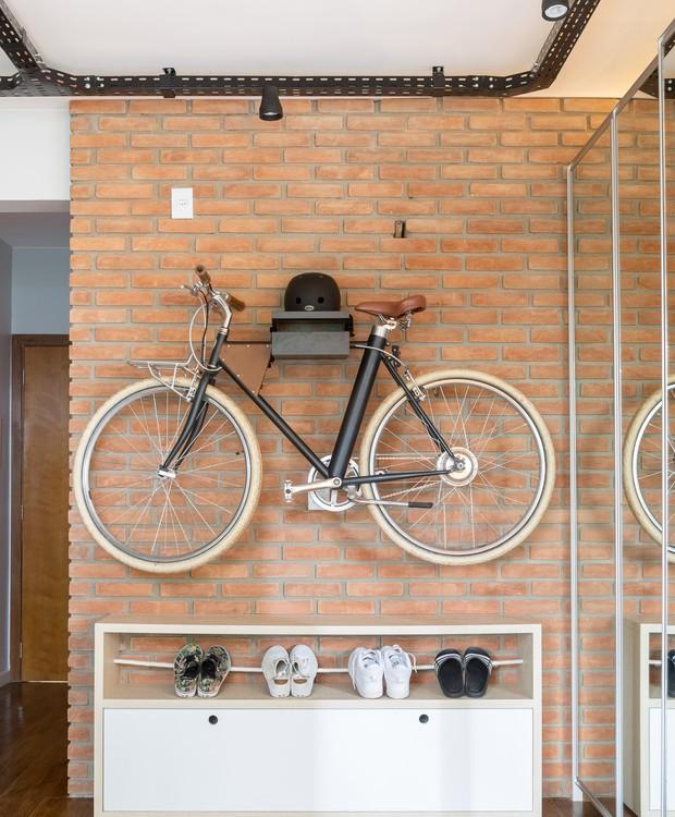 O suporte para bike e capacete também é obra da Caminho Oficina. Com a bicicleta elevada sobrou espaço para uma sapateira (Foto: Joana França/Divulgação)