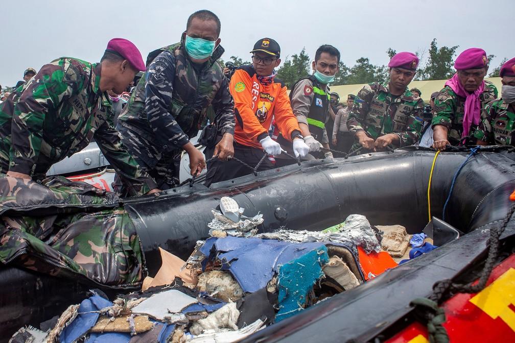 Soldados carregam destroços de avião que caiu na Indonésia, nesta terça-feira (30) — Foto: Antara Foto/Ibnu Chazar via REUTERS
