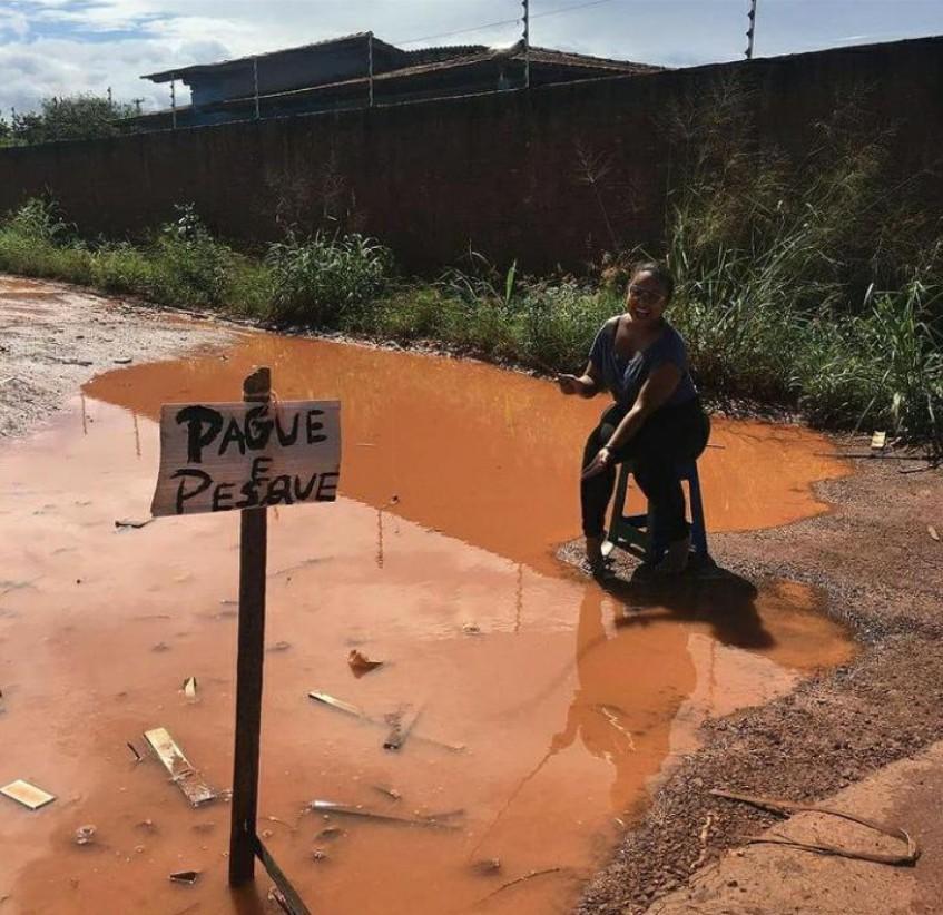Moradora coloca placa de 'pague e pesque' em buraco de rua alagada e ironiza prefeitura de Boa Vista: 'obrigada'