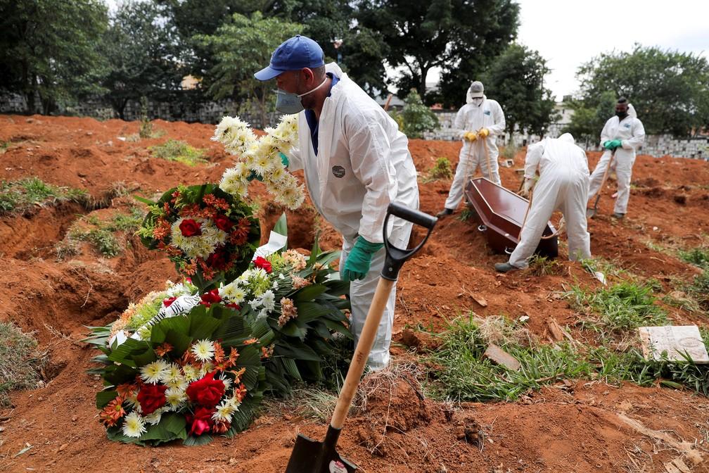 13 de maio - Funcionário do cemitério de Vila Formosa, em São Paulo, carrega uma cruz enquanto outros fazem enterro, durante pandemia de coronavírus (Covid-19) — Foto: Amanda Perobelli/Reuters