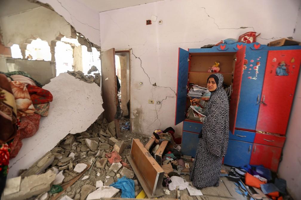 Uma mulher palestina reage enquanto recolhe seus pertences dentro de sua casa destruída após os ataques aéreos e de artilharia israelenses no norte da Faixa de Gaza, na sexta (14)    — Foto: Mohammed Salem/Reuters