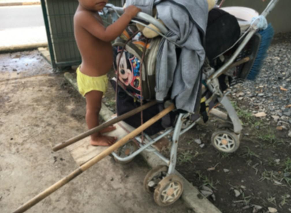 Vivendo na rua, família de sete integrantes, sendo três crianças, adaptou carrinho de bebê para carregar seus pertences; garoto de 1 ano e meio é irmão de menina de 2 anos alvo cuja avó foi abordada para que a vendesse por R$ 2 mil  — Foto: Emily Costa/G1 RR