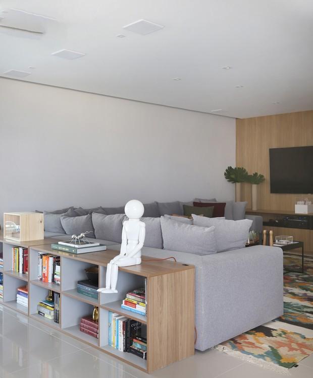 Home theater | Uma estante baixa se junta ao sofá para dividir os cômodos e criar intimidade na medida certa. Ali, o espaço é mais escuro do que o resto do living, perfeito para relaxar (Foto: Mariana Orsi/ Divulgação)