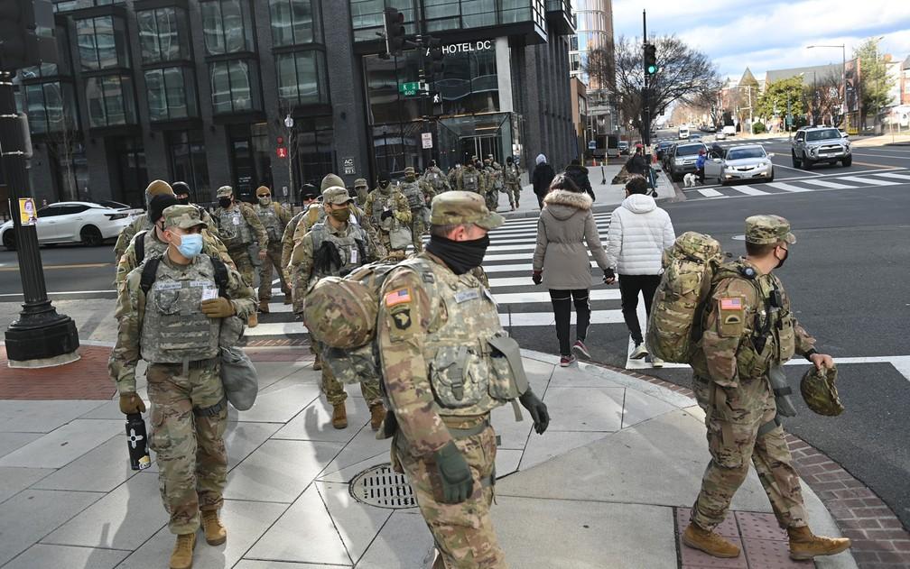 Membros da Guarda Nacional atravessam rua em Washington DC na segunda-feira (18) — Foto: Brendan Smialowski/AFP