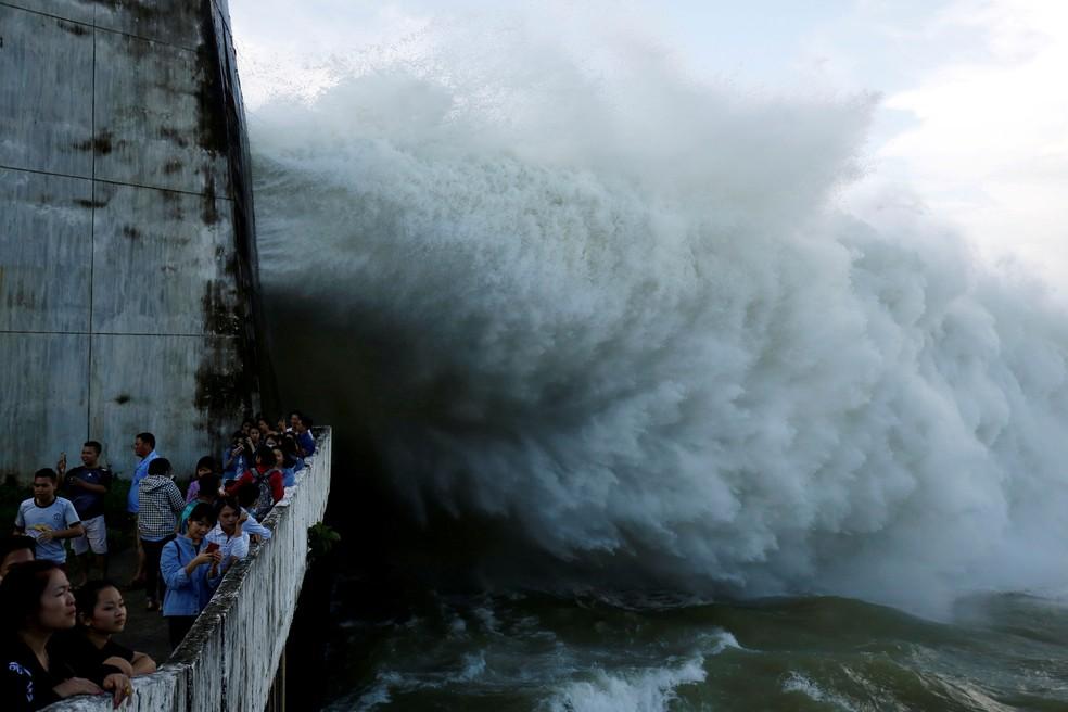 Pessoas observam a abertura dos portões da usina hidrelétrica de Hoa Binh, após fortes chuvas causada por uma depressão tropical na província de Hoa Binh, perto da capital Hanói, no Vietnã (Foto: Kham TPX/Reuters)