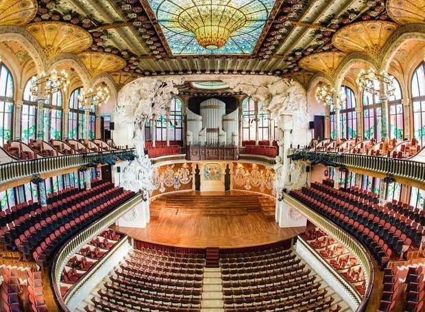 O palácio da música em Barcelo é coberto por um teto vitral de mosaico em tons amarelados (Foto: Palau Música/ Reprodução)