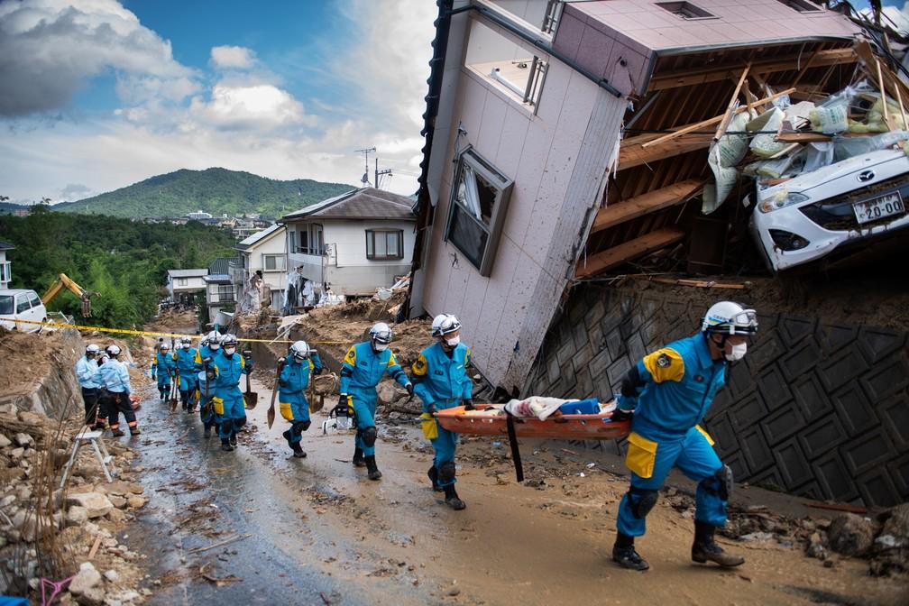 Policiais chegam para limpar os escombros de uma rua atingida pela inundação em Kumano, no Japão. Equipes de resgate trabalham para alcançar moradores presos após as chuvas devastadoras que mataram pelo menos 81 pessoas (Foto: Martin Bureau/AFP)
