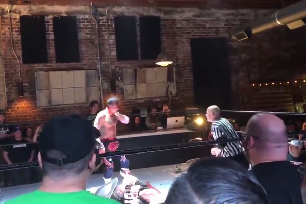 O ator David Arquette com a mão no pescoço após ser ferido durante seu confronto com o lutador profissional Nick Gage (Foto: Twitter)