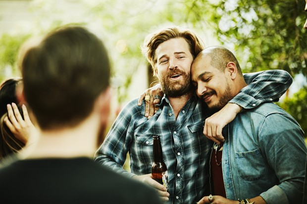 Two friends embracing during backyard party on summer evening (Foto: Getty Images)