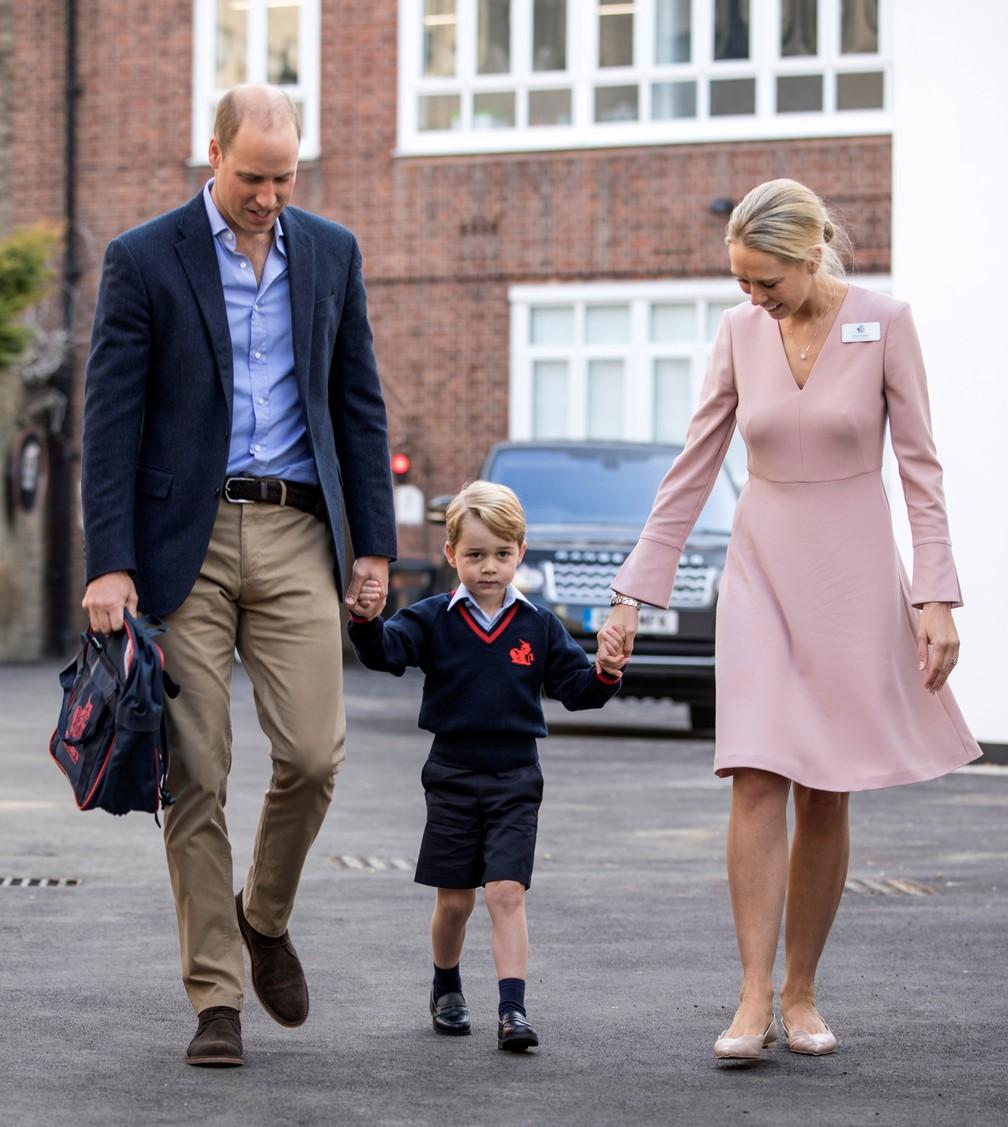 Príncipe George segura as mãos do seu pai, príncipe William, e Helen Haslem, diretora da escola em Battersea (Foto: Richard Pohle/Pool/Reuters)
