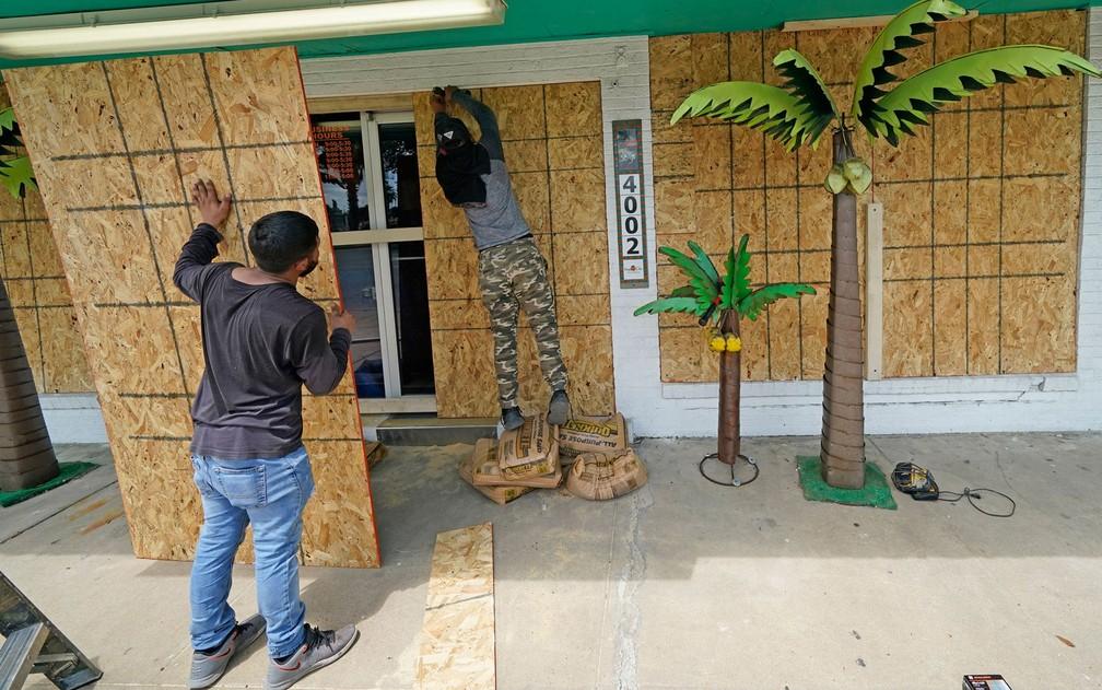 Issac Alvarado (direota) e Kevin Enriquez colocam tapumes em uma loja de decorações em Galveston, Texas, antes da chegada do furacão Laura, na terça-feira (25) — Foto: AP Photo/David J. Phillip