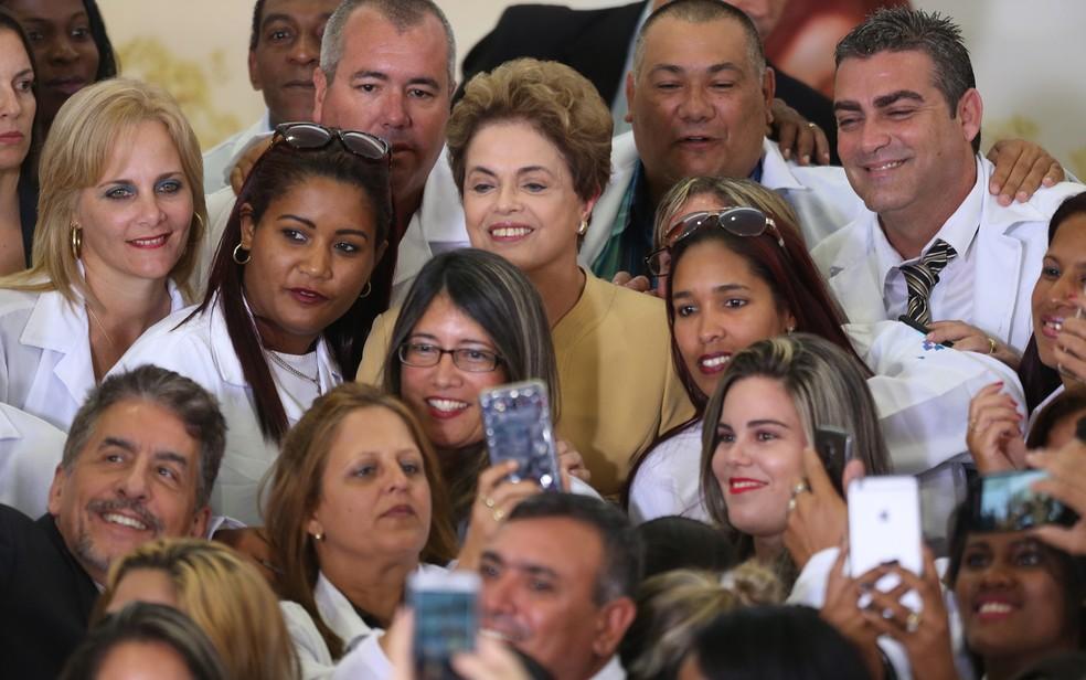 Programa Mais Médicos foi criado pelo governo de Dilma Rousseff - na imagem, tirada em 2016, Dilma lança nova fase do programa e é cercada por profissionais, alguns cubanosA presidente Dilma Rousseff anúnciou nesta sexta (29) a prorrogação do Programa Mais Médicos — Foto: Dida Sampaio/Estadão Conteúdo