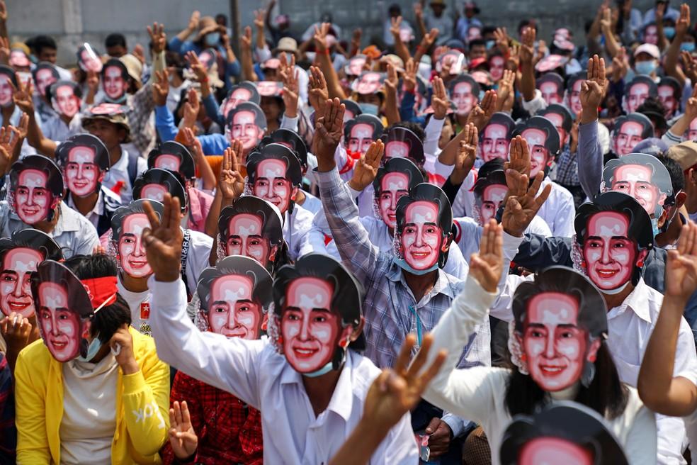 Manifestantes usando máscaras com o rosto de Aung San Suu Kyi protestam na cidade de Yangon, em Mianmar — Foto: Stringer/Reuters