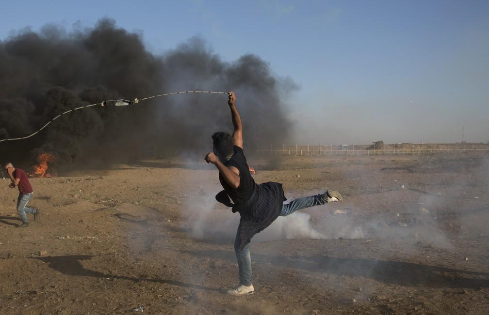 -  Manifestante palestino lança bomba de gás lacrimogêneo contra soldados israelenses na fronteira com a Faixa de Gaza  Foto: Khalil Hamra/AP Photo