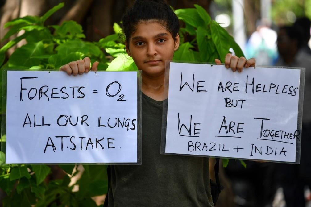 """Manifestante segura cartazes com os dizeres """"Forestas = oxigênio. Todos os nossos pulmões em risco"""" e """"Estamos desamparados, mas estamos juntos. Brasil + Índia"""" durante protesto nesta sexta-feira (23) em frente ao consulado brasileiro em Mumbai, na Índia. — Foto: Indranil Mukherjee / AFP"""