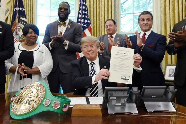 O presidente dos EUA, Donald Trump, ao lado de Sylvester Stallone, com a carta perdoando o boxeador Jack Johnson (Foto: Getty Images)