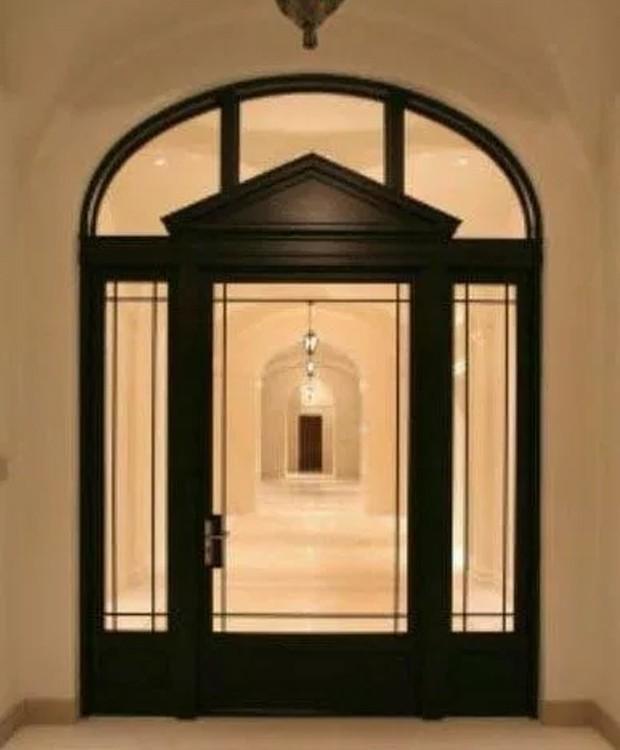 A porta de entrada de vidro é em forma de arco  (Foto: Splashnews/ Reprodução)