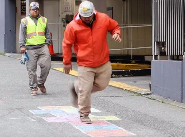 Trabalhador uniformizado interage com a amarelinha (Foto: Reprodução)