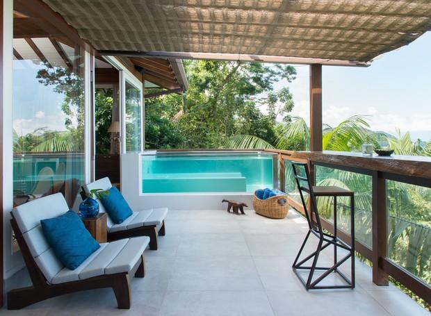Fechada com vidros, a piscina na varanda é praticamente uma extensão da sala de estar - ali os amigos passam horas conversando enquanto apreciam a vista do mar (Foto: Cacá Bratke/Divulgação | Produção Deborah Apsan)