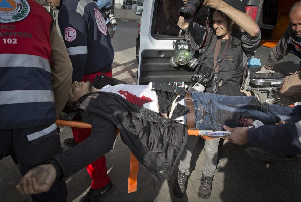 Serviço de emergência transporta palestino que foi baleado pela polícia israelense depois de atacar agentes nesta sexta-feira (15) em Ramallah (Foto: Nasser Nasser/ AP Photo)