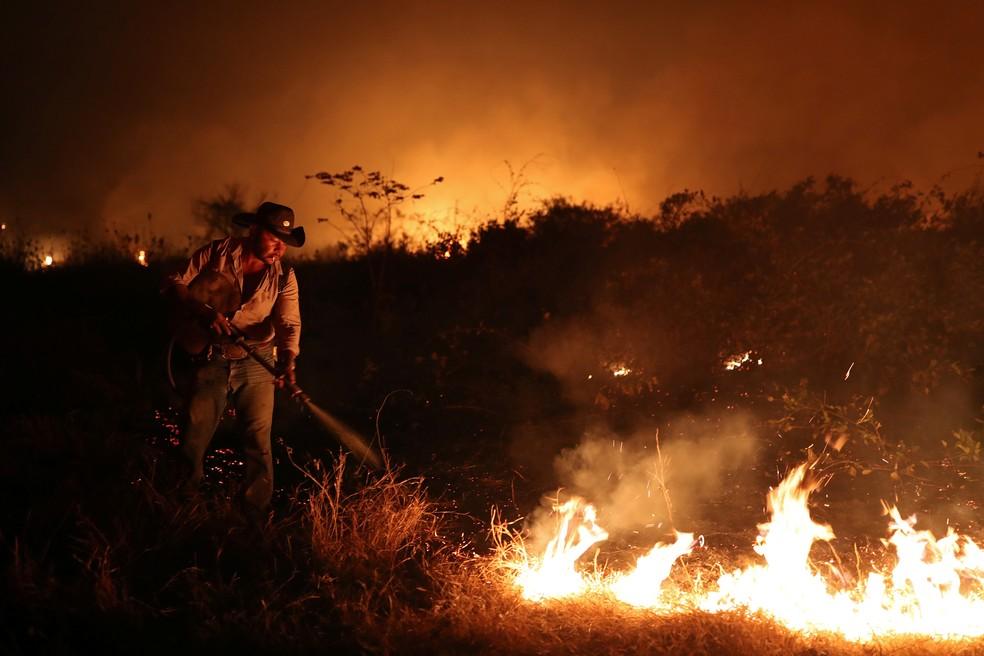 Sebastião Baldi Silva Junior, de 40 anos, tenta apagar um incêndio em uma fazenda no Pantanal, a maior área úmida do mundo, em Poconé (MT) — Foto: Amanda Perobelli/Reuters
