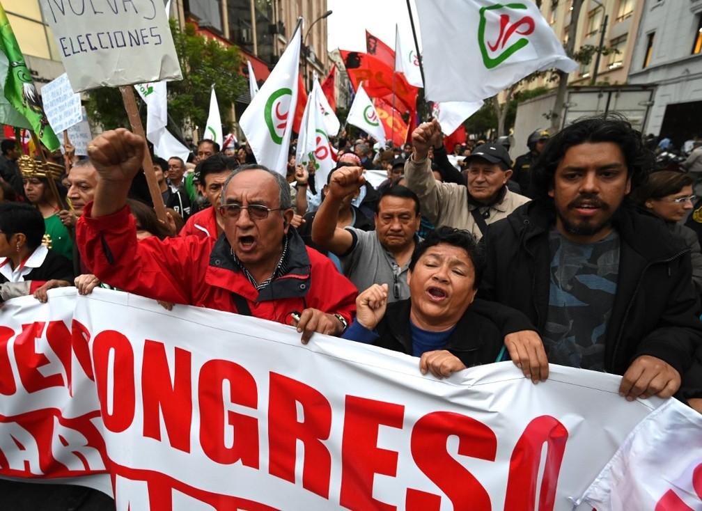 Manifestantes marcham na segunda-feira (30), em Lima, a favor de novas eleições após a dissolução do Congresso peruano. — Foto: Cris Bouroncle/AFP