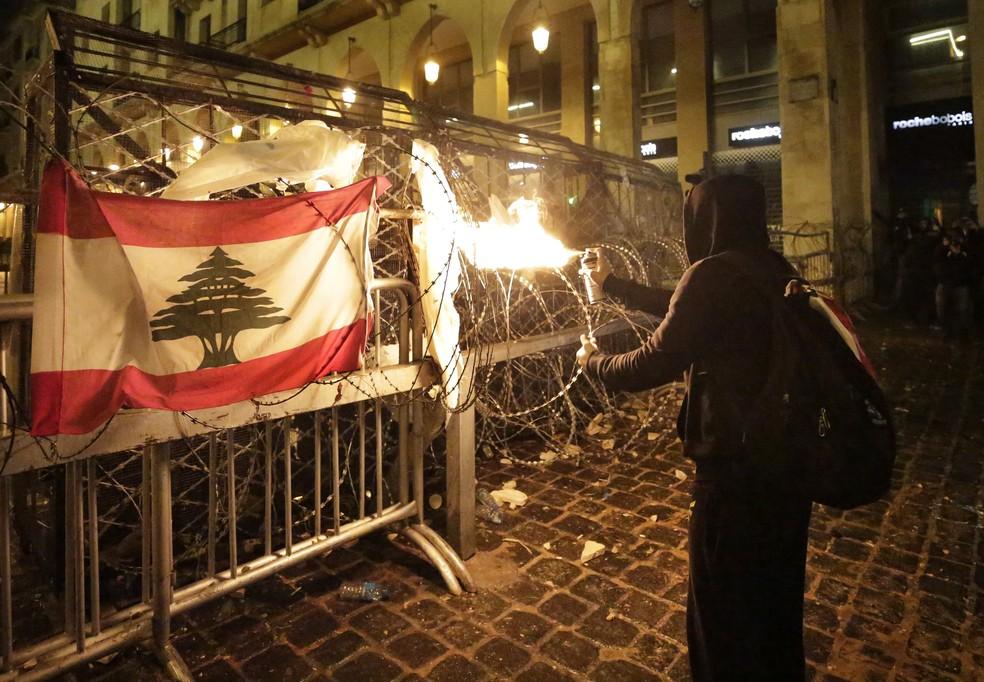 Manifestante lança chamas a partir de spray contra policiais que cercam o Parlamento do Líbano, em Beirute, neste domingo (19) — Foto: Hassan Ammar/AP Photo