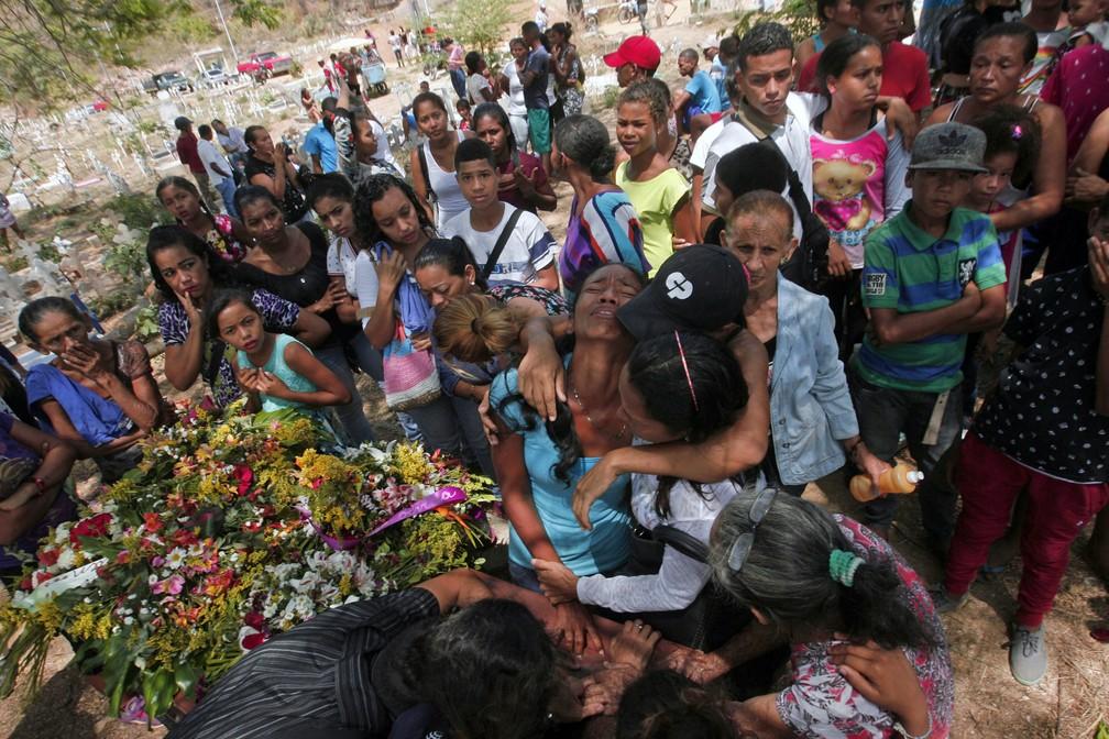 Parentes se emocionam durante enterro de detento morto em incêndio em prisão na cidade de Valência, na Venezuela (Foto: Juan Carlos Hernandez/AFP)