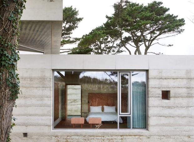 Os traços minimalistas e os tons sóbrios permitem com que o verde do lado de fora dê cor a toda a construção (Foto: Deezen/ Reprodução)