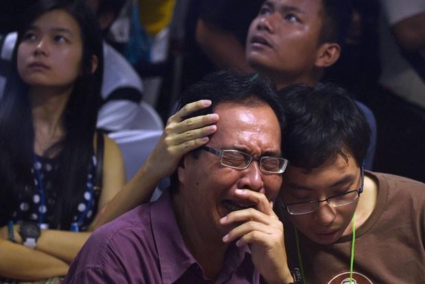 Parentes de passageiros do avião da AirAsia que caiu no mar choram no aeroporto de Juanda, em Surabaya, na Indonésia, ao receberem a notícia da localização dos destroços da aeronave nesta terça-feira (30) (Foto: Manan Vatsyayana/AFP)