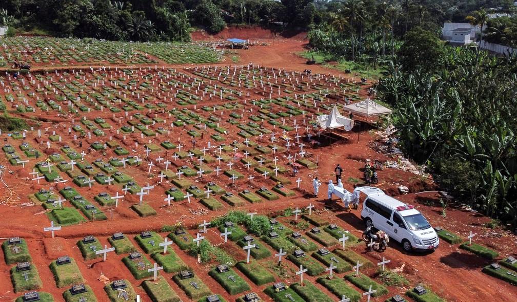 Vista aérea de um cemitério em Jacarta, na Indonésia, mostra coveiros com roupas de proteção carregar um caixão com uma vítima de Covid durante a pandemia do novo coronavírus — Foto: Willy Kurniawan/Reuters