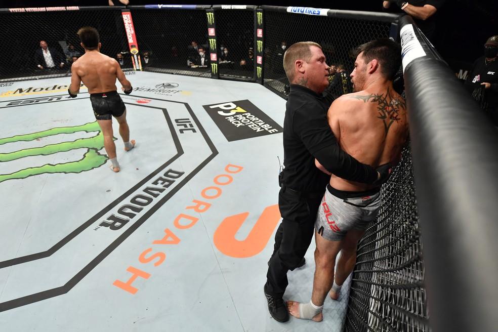 Dominick Cruz reclama da interrupção com o árbitro da luta, Keith Peterson — Foto: Getty Images