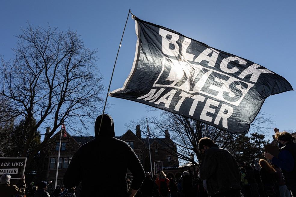 Manifestantes erguem a bandeira do Black Lives Matter durante protesto por justiça para George Floyd, em St. Paul, Minnesota — Foto: Kerem Yucel/AFP