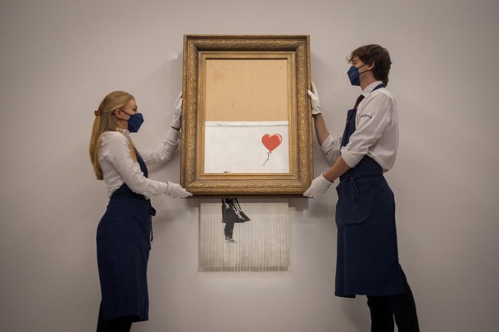 """Funcionários da casa de leilões Sotheby's apresentam a obra """"Menina do balão"""", de Banksy. Nova versão da obra será vendida em leilão em 14 de outubro— Foto: Tolga Akmen / AFP"""