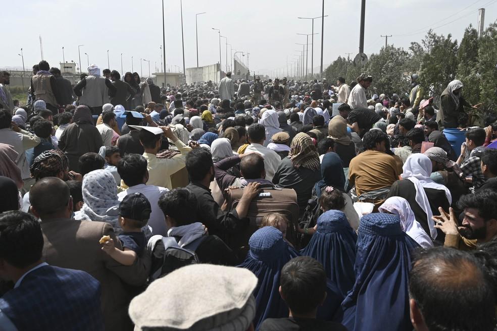 Afegãos se reúnem em uma estrada perto da parte militar do aeroporto de Cabul, nesta sexta-feira (20) — Foto: Wakil Kohsar/AFP