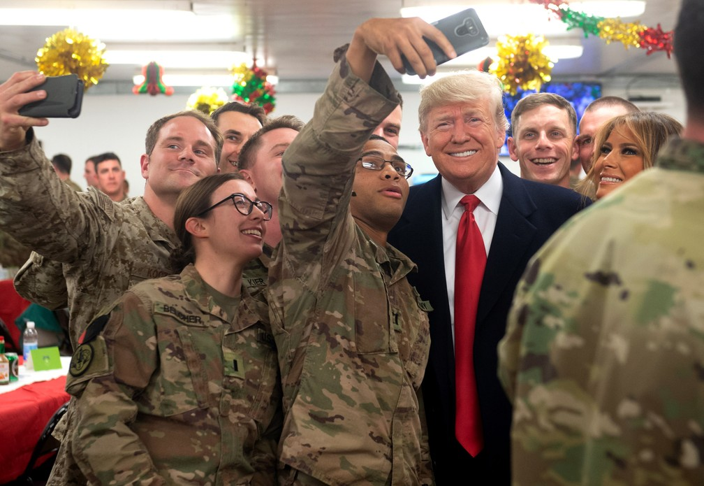 O presidente dos EUA Donald Trump e a primeira-dama Melania Trump tiram uma selfie com militares dos EUA durante uma viagem não anunciada à Base Aérea de Al Asad, no Iraque, em 26 de dezembro de 2018  — Foto: Saul Loeb/AFP/Arquivo