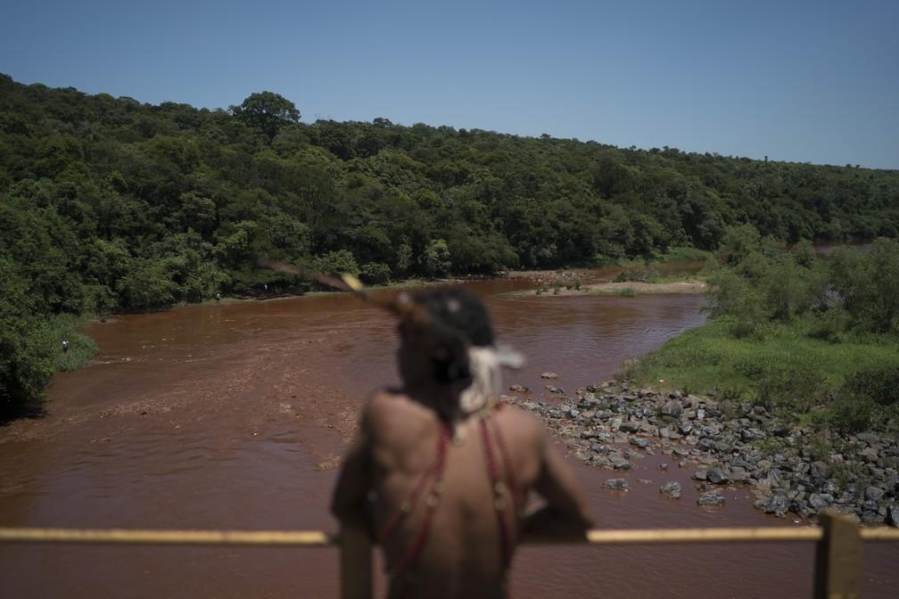 29 de janeiro - Hayo, chefe da comunidade indígena Pataxo Hã-hã-hãe, observa o rio Paraopeba com as águas tingidas pela lama — Foto: Leo Correa/AP