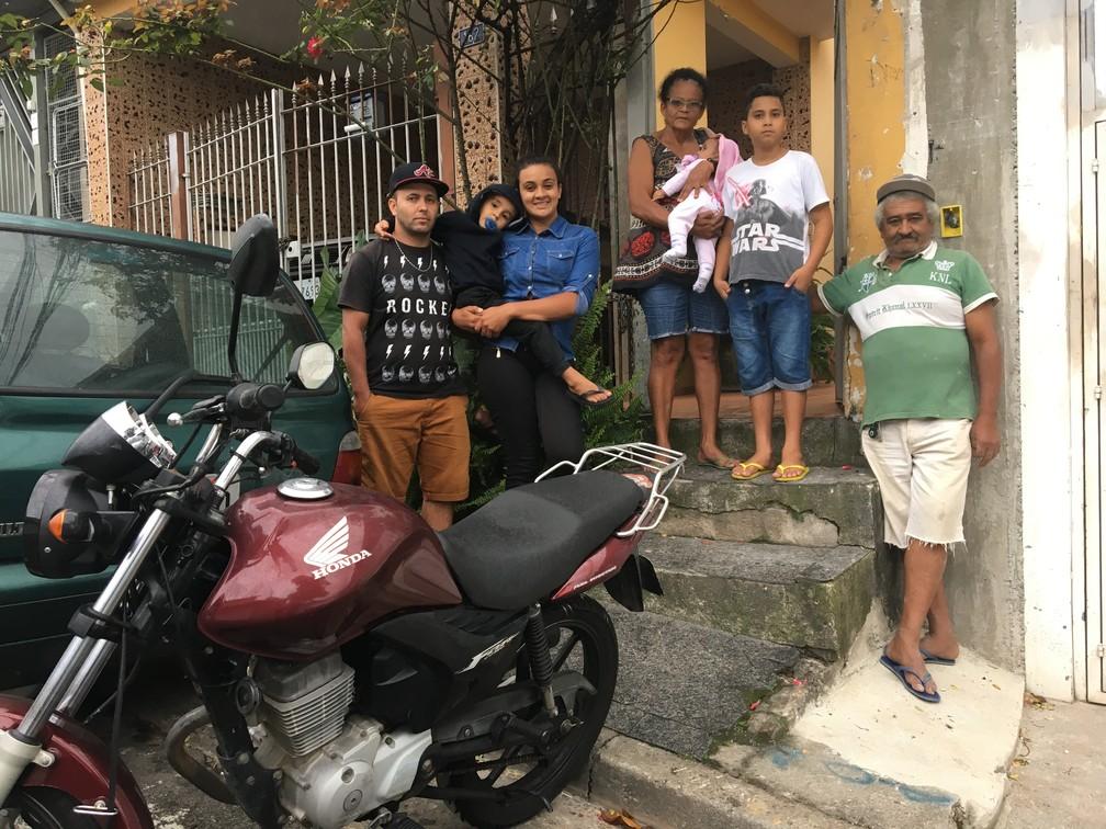 Leiliane posa ao lado da família na fachada da casa da mãe, em Pirituba, para onde se mudou após ser diagnosticada com doença rara — Foto: Glauco Araújo/G1