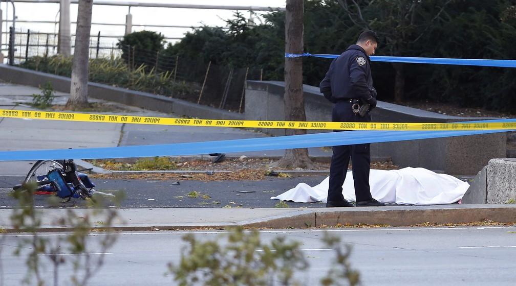 Policial é visto ao lado de corpor coberto perto de uma ciclovia nesta terça-feira (31) em Nova York (Foto: AP Photo/Bebeto Matthews)