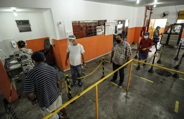 NITEROI, BRAZIL - AUGUST 05: People wait in line while maintaining social distance at a popular soup kitchen on August 5, 2020 in Niteroi, Brazil. Employees received special training to ensure the safety of visitors. The site will intensify the cleaning p (Foto: Getty Images)