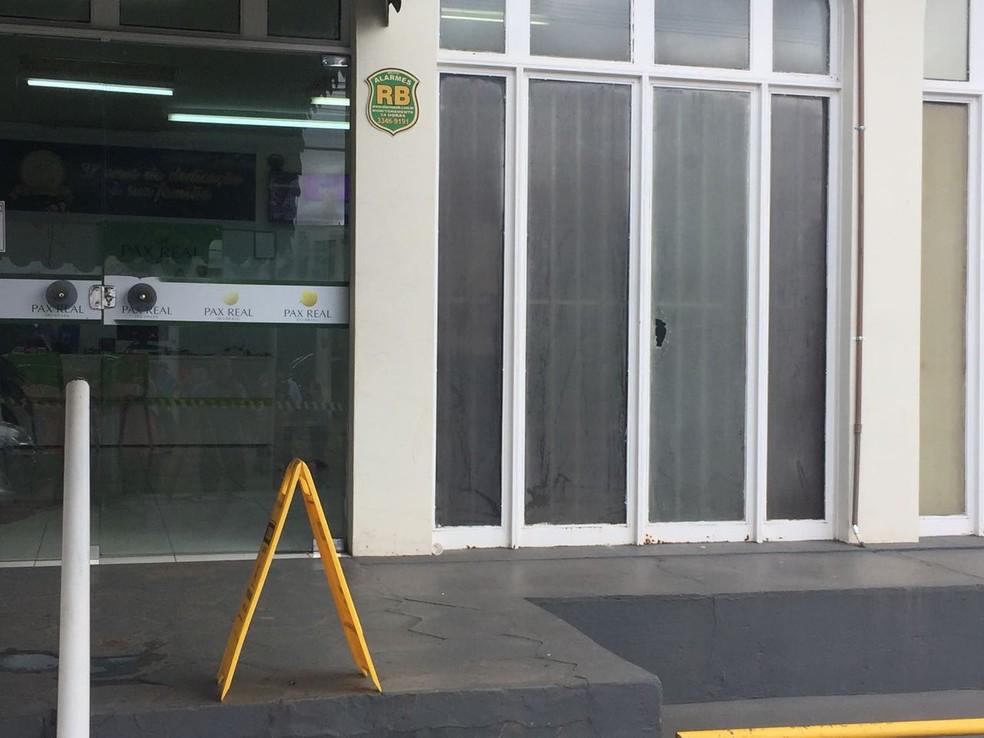 Vidro da fachada da empresa, em Campo Grande, MS, também foi atingido (Foto: Graziela Rezende/ TV Morena)