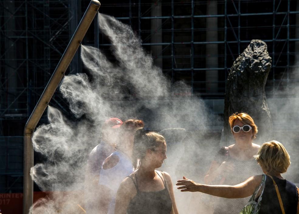 Mulheres se refrescam com borrifador de água público em Lille, na França, durante onda de calor na Europa (Foto: Philippe Huguen/AFP)