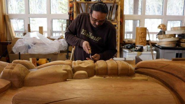 O artista indígena Keith Wolfe Smarch usa o deserto de Carcross como inspiração para talhar madeira (Foto: MIKE MACEACHERAN - BBC news)