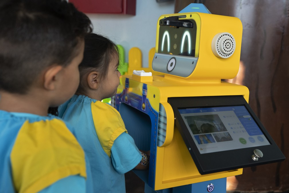 Crianças checam a temperatura em um robô em uma demonstração em uma escola primária em Madri, no dia 4 de setembro, em meio à pandemia da Covid-19. — Foto: Paul White/AP