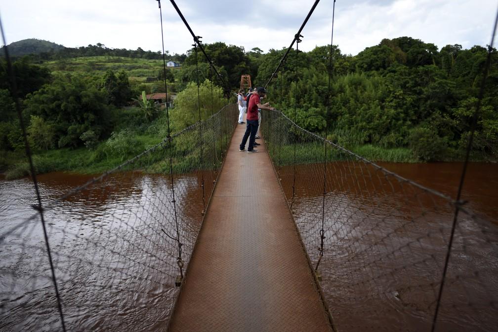 Pessoas observam o rio Paraopeba, afetado pela lama, um dia depiois depois do rompimento da barragem da Vale, em Brumadinho. — Foto: Douglas Magno/AFP