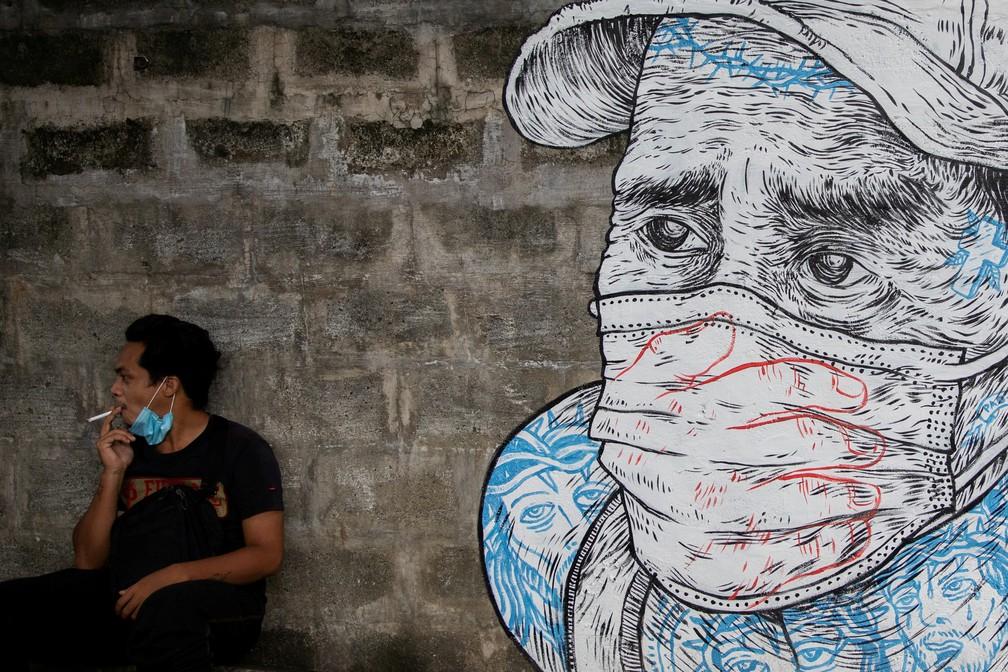 30 de julho - Homem fuma um cigarro ao lado de mural de outro homem com máscara protetora, em meio ao surto de coronavírus (COVID-19), em Quezon City, Manila, Filipinas — Foto: Eloisa Lopez/Reuters