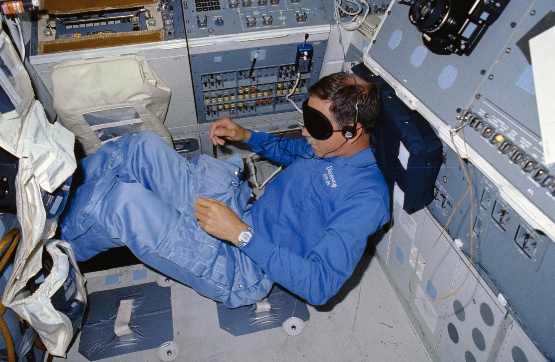 Richard O. Covey, piloto da STS-26, dorme apoiando sua cabeça em painéis durante a missão da NASA (Foto: NASA)