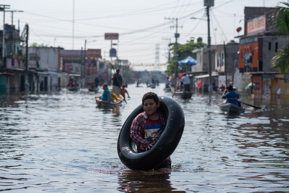 Menino anda carregando pneu no ombro em meio a rua alagada após chuvas fortes na cidade de Villahermosa, no estado mexicano de Tabasco, no dia 11 de novembro. — Foto: Angel Hernandez/AFP
