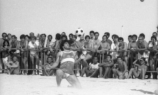 De joelhos, o craque Maradona mata a bola no peito, em jogo de futevôlei
